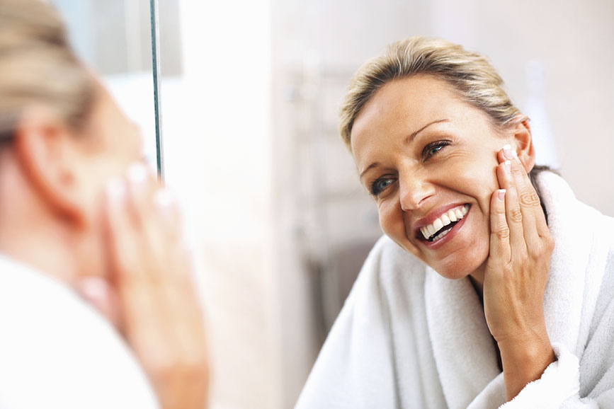 Happy mature woman admiring herself in the mirror